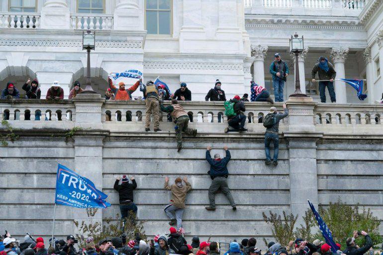 Simpatizantes del presidente Donald Trump escalan un muro del Capitolio federal, el miércoles 6 de enero de 2021, en Washington.