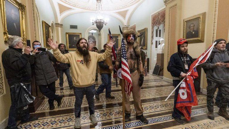 Un supuesto seguidor de Trump sostiene un maletín y una bandera en apoyo al magnate neoyorquino y un joven de pelo largo y barba exhibe un prominente tatuaje que vincularon con Antifa en varias publicaciones de Internet